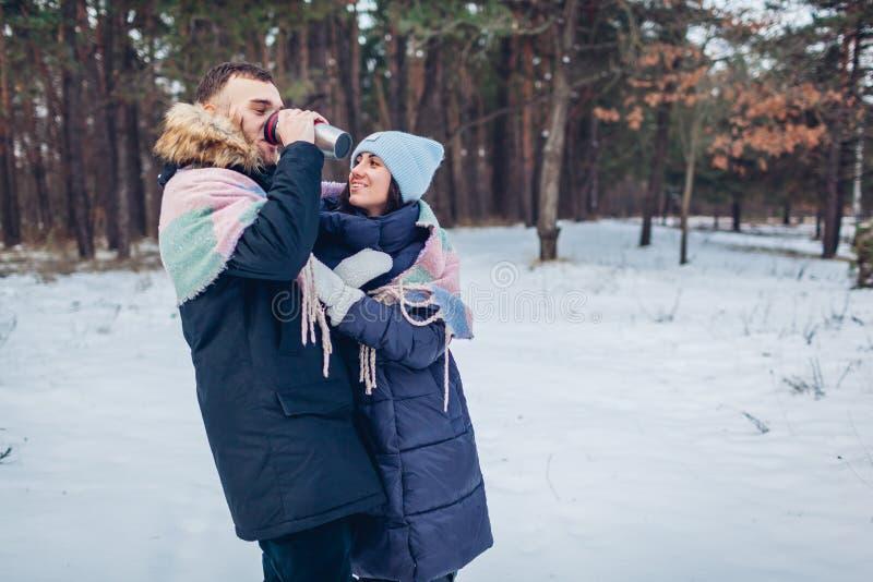 Όμορφο αγαπώντας ζεύγος που περπατά στο χειμερινό δάσος από κοινού Άνθρωποι που πίνουν το καυτό τσάι στα thermos στοκ εικόνες με δικαίωμα ελεύθερης χρήσης