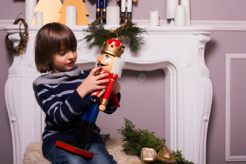 Όμορφο αγόρι με το παιχνίδι στο υπόβαθρο Χριστουγέννων στοκ φωτογραφία
