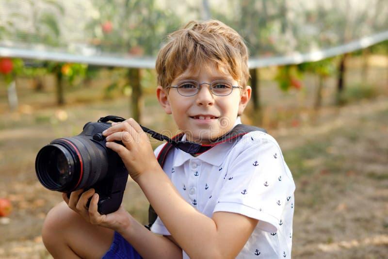 Όμορφο αγόρι παιδιών με τα γυαλιά που κάνει τις εικόνες με τη χρησιμοποίηση της ψηφιακής επαγγελματικής κάμερας Λίγο παιδί που μα στοκ εικόνες