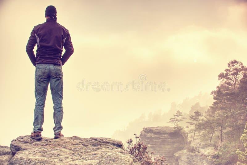 Όμορφο αθλητικό άτομο, ένας τουρίστας, παραμονή στο βράχο συνόδου κορυφής Άγρια υδρονέφωση στοκ εικόνα