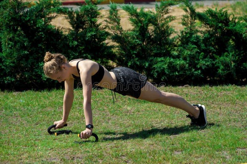 Όμορφο αθλητικό κορίτσι που κάνει την ικανότητα στη φύση στοκ εικόνα