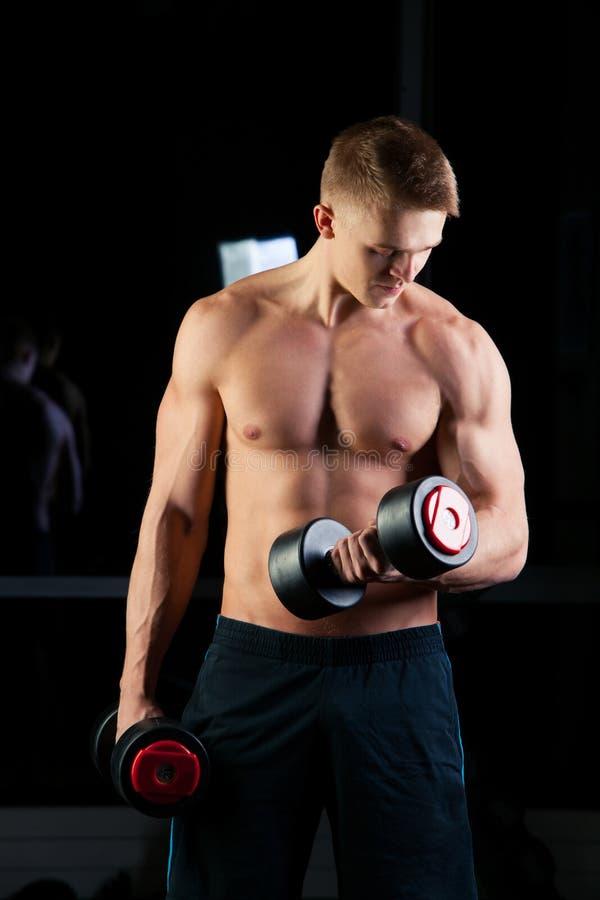 Όμορφο αθλητικό άτομο δύναμης με τον αλτήρα που κοιτάζει με βεβαιότητα προς τα εμπρός Ισχυρό bodybuilder έξι πακέτο, τέλεια ABS στοκ φωτογραφίες με δικαίωμα ελεύθερης χρήσης