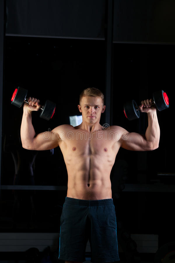 Όμορφο αθλητικό άτομο δύναμης με τον αλτήρα που κοιτάζει με βεβαιότητα προς τα εμπρός Ισχυρό bodybuilder έξι πακέτο, τέλεια ABS στοκ εικόνα