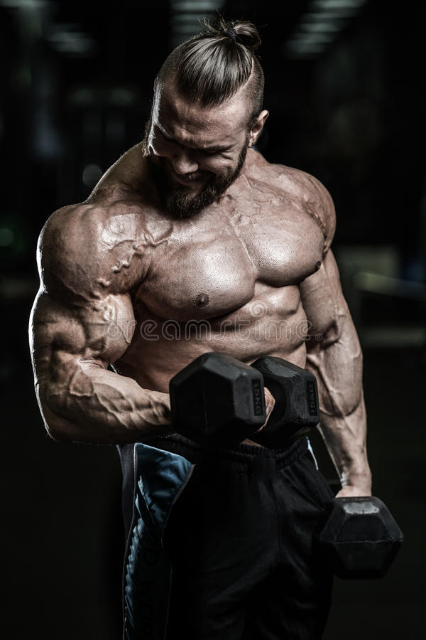Όμορφο αθλητικό άτομο δύναμης στη διατροφή που εκπαιδεύει αντλώντας επάνω τους μυς στοκ εικόνες