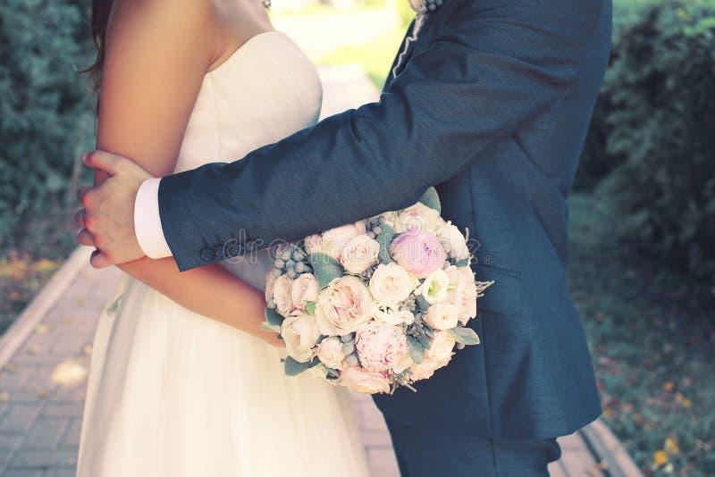 Όμορφο αισθησιακό γαμήλιο ζεύγος και ευγενής ανθοδέσμη των λουλουδιών στοκ εικόνες