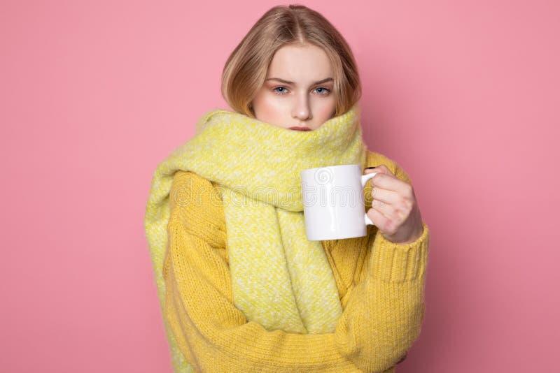 Όμορφο αισθησιακό κορίτσι με την ξανθή τρίχα και μπλε μάτια που φορούν το κίτρινα πουλόβερ και το μαντίλι στοκ εικόνα
