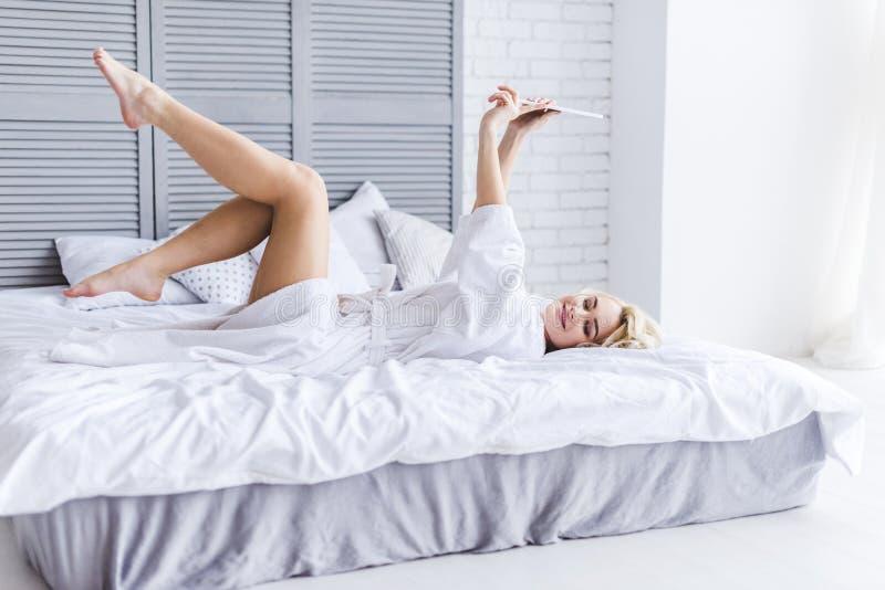 όμορφο αισθησιακό κορίτσι στο μπουρνούζι που βρίσκεται στο κρεβάτι και τη χρησιμοποίηση στοκ φωτογραφία