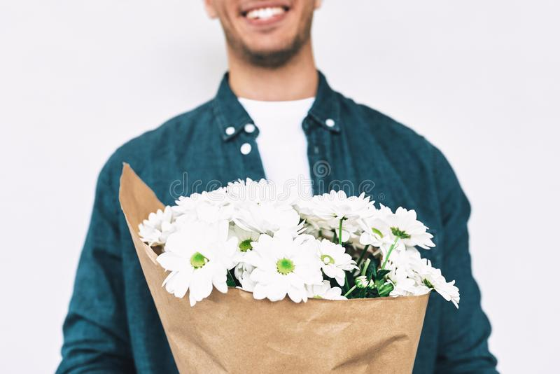 Όμορφο αρσενικό με μια δέσμη των λουλουδιών που προετοιμάζονται για μια ημερομηνία με τη φίλη Νέο ευτυχές άτομο που χαμογελά και  στοκ φωτογραφία με δικαίωμα ελεύθερης χρήσης