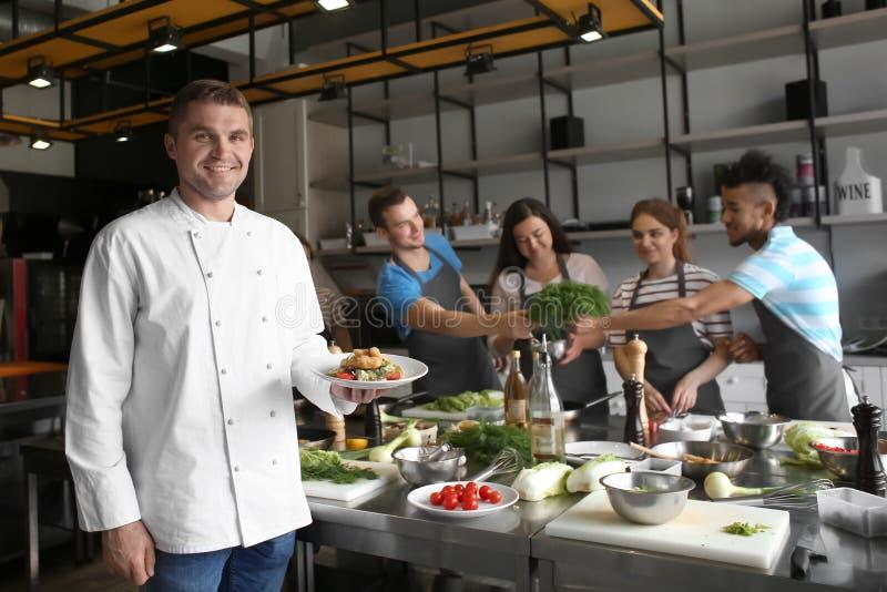Όμορφο αρσενικό πιάτο εκμετάλλευσης αρχιμαγείρων με το έτοιμο πιάτο κατά τη διάρκεια των μαγειρεύοντας κατηγοριών στοκ φωτογραφία με δικαίωμα ελεύθερης χρήσης