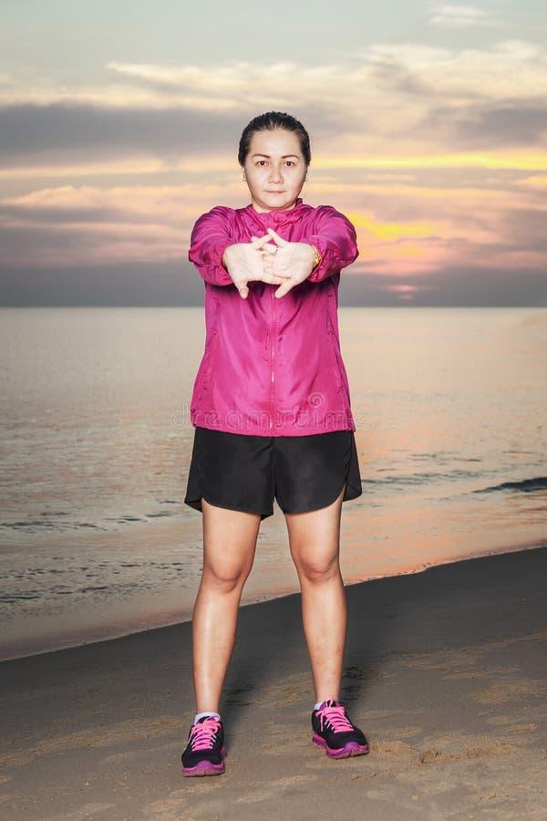 Όμορφο ασιατικό κορίτσι που κάνει τις ασκήσεις στην παραλία ενάντια στο σκηνικό του ηλιοβασιλέματος και της θάλασσας στοκ φωτογραφία