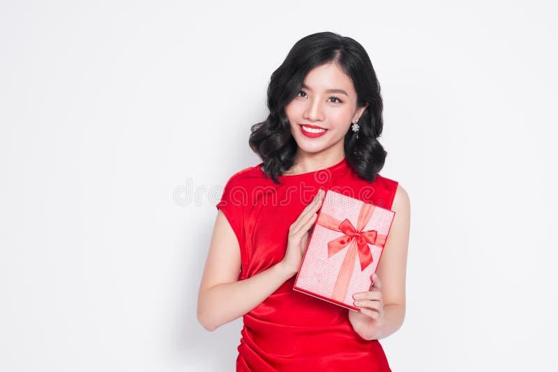 Όμορφο ασιατικό κορίτσι που κρατά ένα παρόν στα χέρια και το χαμόγελό της στοκ φωτογραφία