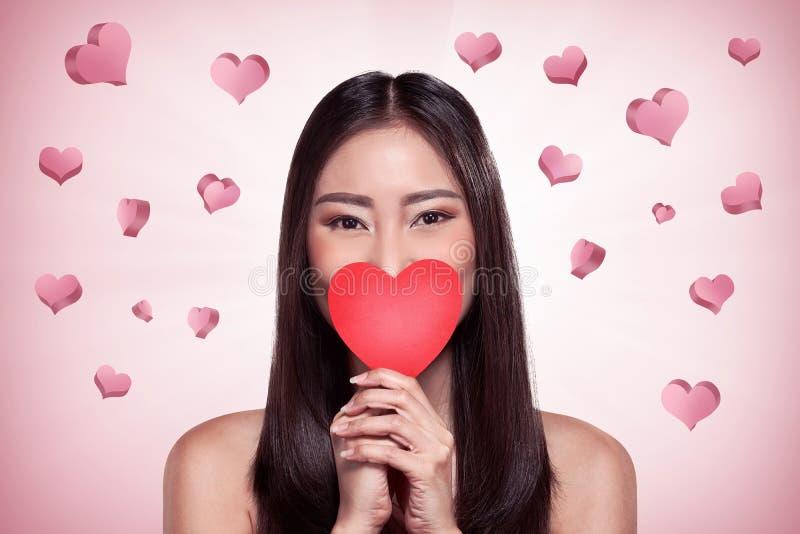 Όμορφο ασιατικό κορίτσι που κρατά την κόκκινη καρδιά στοκ εικόνες