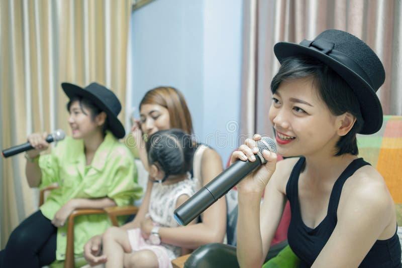 Όμορφο ασιατικό νεώτερο τραγούδι καραόκε τραγουδιού γυναικών στο σπίτι, fami στοκ εικόνες