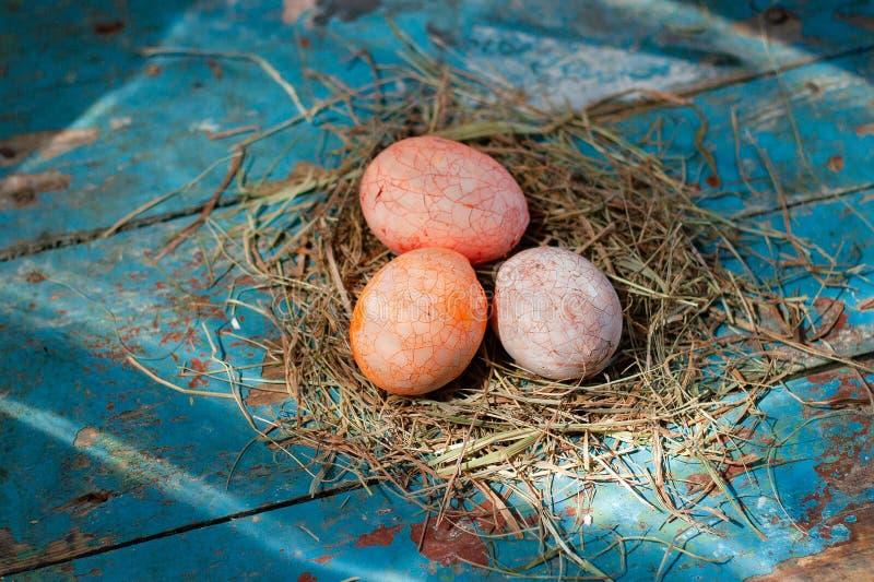 Όμορφο αυγό χρώματος Πάσχας πολυ στο άχυρο στο ξύλινο υπόβαθρο, έννοια ημέρας Πάσχας στοκ εικόνες