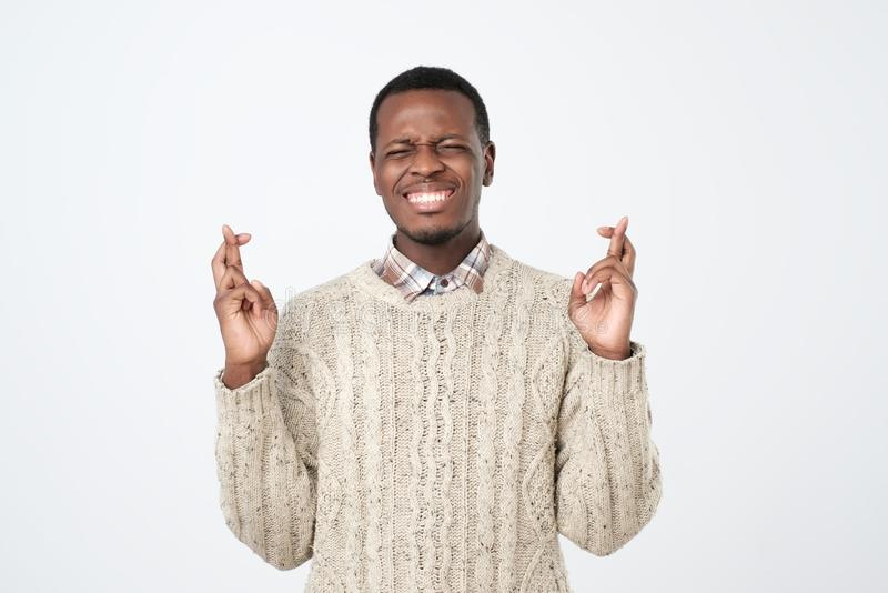 Όμορφο αφρικανικό αρσενικό που στέκεται με τα διασχισμένα δάχτυλα που έχουν την παράκληση της έκφρασης στοκ φωτογραφία με δικαίωμα ελεύθερης χρήσης