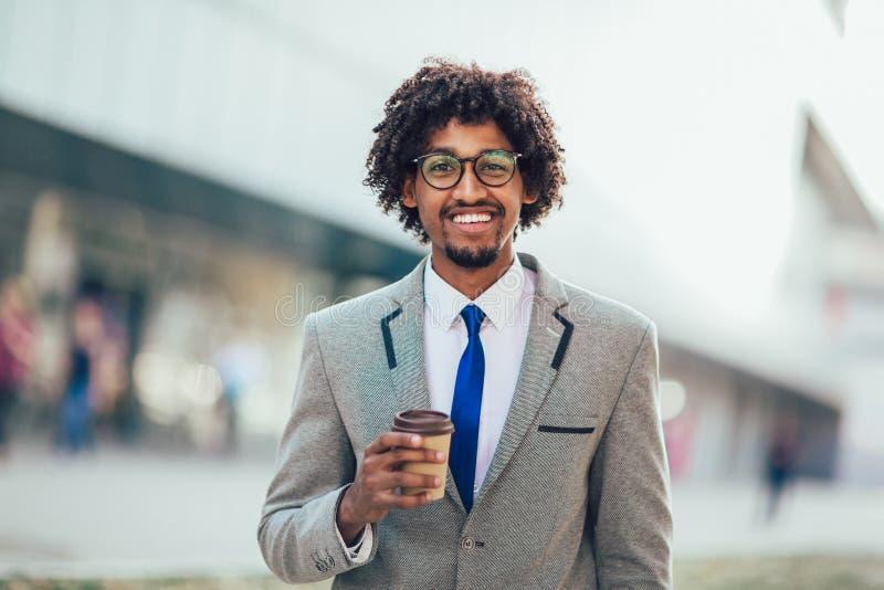 Όμορφο αφρικανικό επιχειρησιακό άτομο έξω με το φλυτζάνι καφέ στοκ εικόνες