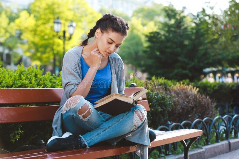 Όμορφο αφρικανικό κορίτσι Thouhtful που διαβάζει το βιβλίο στοκ εικόνες