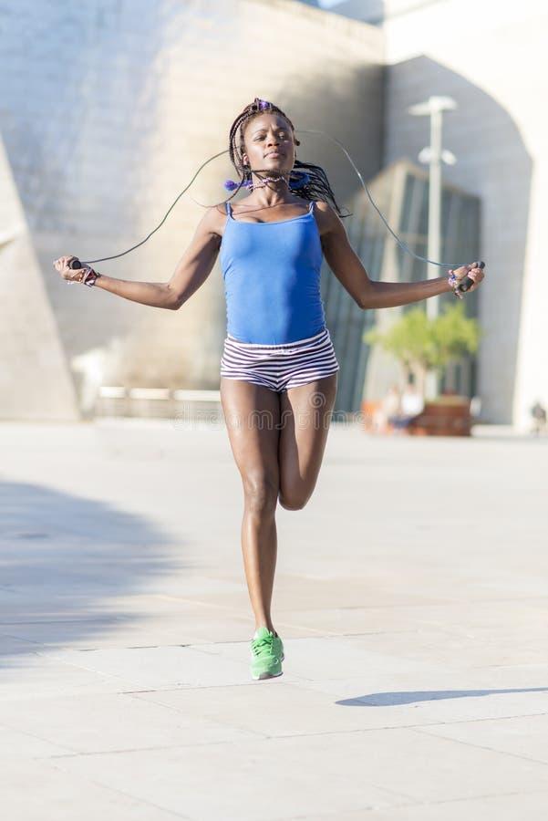 Όμορφο αφρικανικό σχοινί άλματος αθλητριών, υγιής τρόπος ζωής ομο στοκ εικόνες