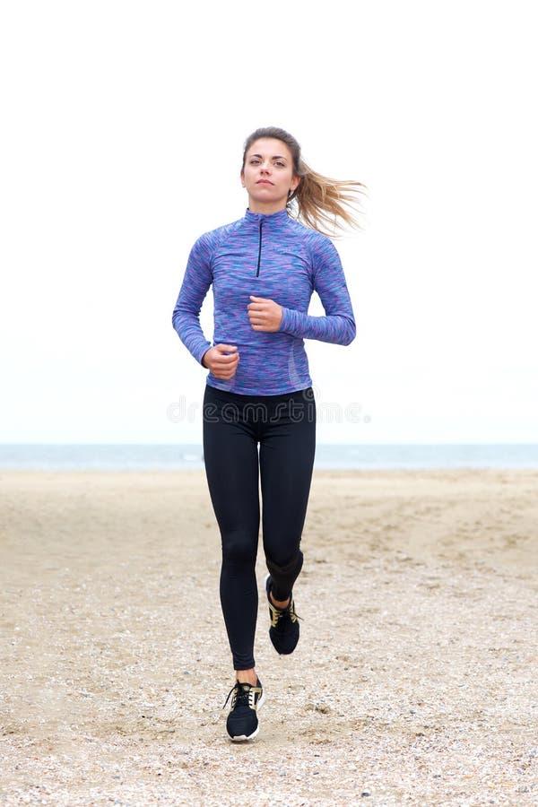 Όμορφο βέβαιο θηλυκό jogger στην άμμο στοκ εικόνα