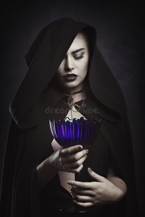 Όμορφο βαμπίρ με ένα τελετουργικό φλυτζάνι στοκ φωτογραφίες