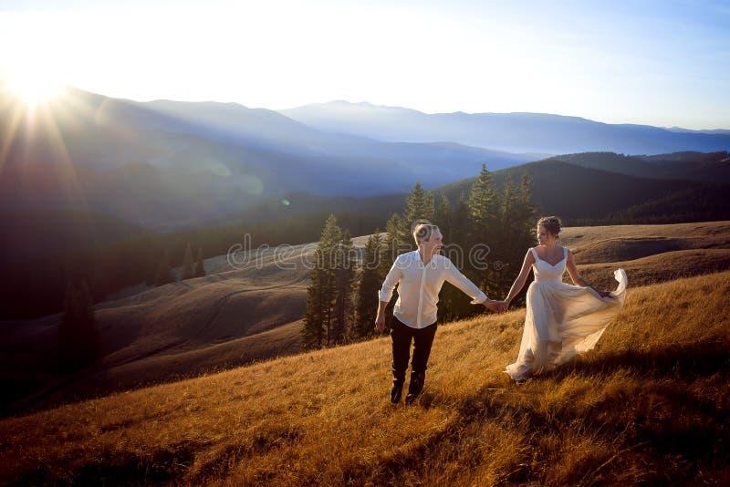 Όμορφο γαμήλιο ζεύγος που τρέχει και που έχει τη διασκέδαση στον τομέα που περιβάλλεται από τα βουνά στοκ εικόνες