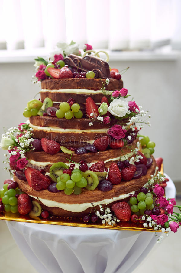 Όμορφο γαμήλιο κέικ με τα φρούτα στον πίνακα στοκ φωτογραφία με δικαίωμα ελεύθερης χρήσης