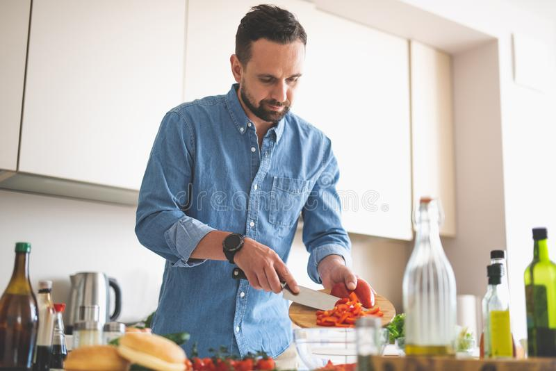 Όμορφο γενειοφόρο άτομο που βάζει το τεμαχισμένο κόκκινο πιπέρι στο κύπελλο στοκ φωτογραφία με δικαίωμα ελεύθερης χρήσης