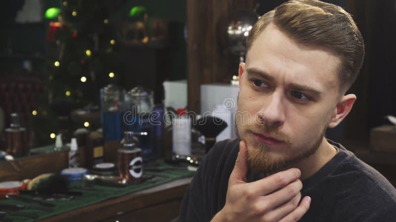 Όμορφο γενειοφόρο άτομο που εξετάζει το νέο κούρεμά του στο barbershop στοκ φωτογραφίες με δικαίωμα ελεύθερης χρήσης