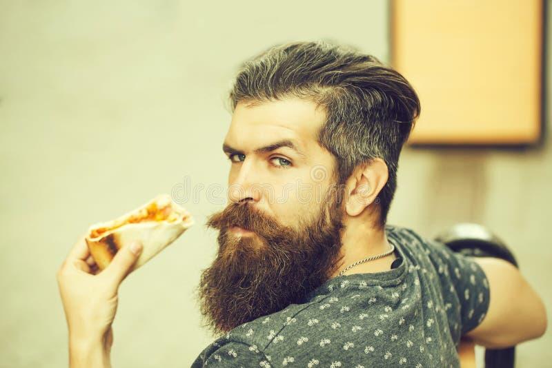 Όμορφο γενειοφόρο άτομο που τρώει την πίτσα στοκ εικόνα με δικαίωμα ελεύθερης χρήσης