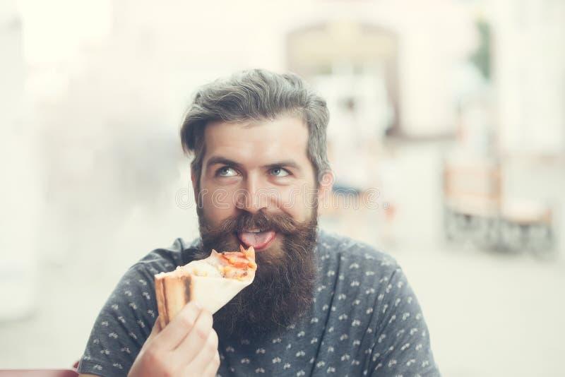 Όμορφο γενειοφόρο άτομο που τρώει την πίτσα στοκ εικόνες με δικαίωμα ελεύθερης χρήσης