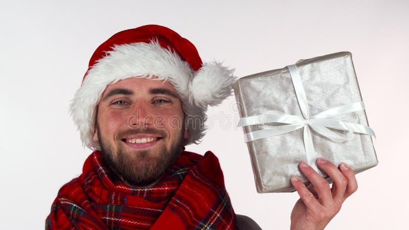 Όμορφο γενειοφόρο άτομο στο χαμόγελο καπέλων Χριστουγέννων, που κρατά ψηλά ένα παρόν στοκ φωτογραφίες