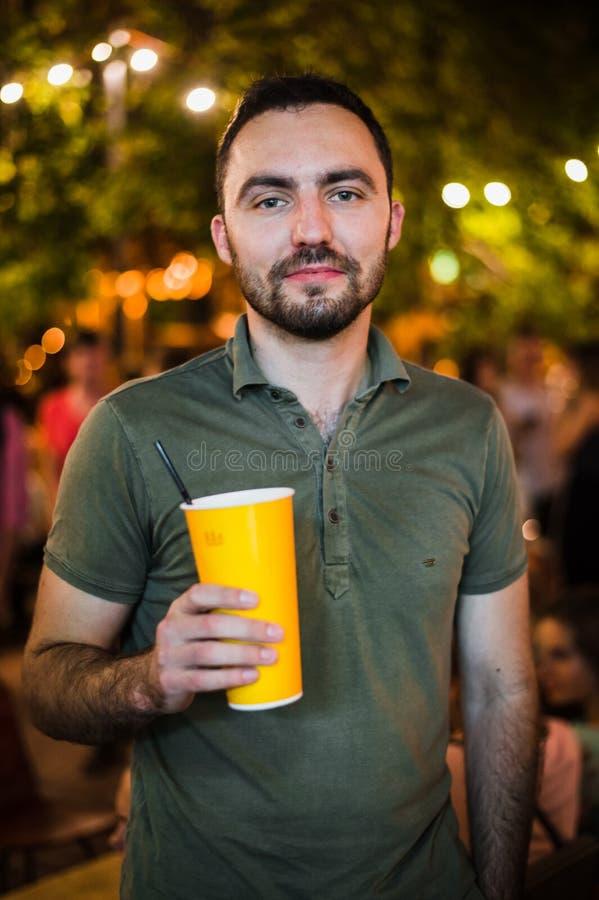 Όμορφο γενειοφόρο ευρωπαϊκό άτομο που πίνει coctail ή μπύρα στο υπαίθριο κόμμα νύχτας καφέδων οδών στο πάρκο στοκ εικόνες