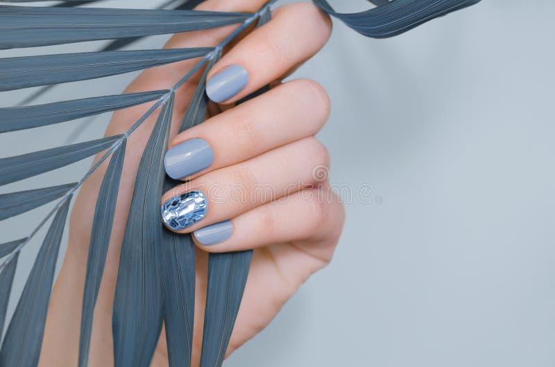 Όμορφο γυναικείο χέρι με μπλε σχεδίαση νυχιών στοκ εικόνες με δικαίωμα ελεύθερης χρήσης