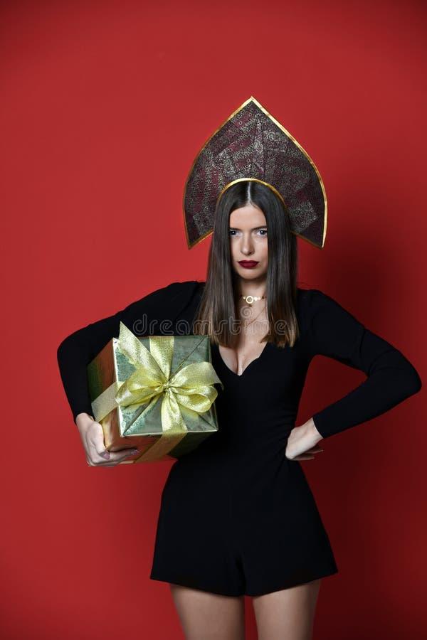 Όμορφο γυναικών κιβώτιο δώρων λαβής χρυσό παρόν στο ρωσικό παραδοσιακό μαύρο καπέλο kokoshnik στοκ φωτογραφίες