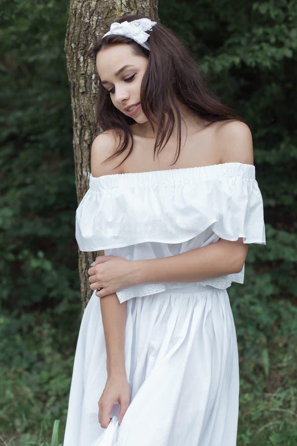 Όμορφο γλυκό κορίτσι με τη σκοτεινή τρίχα στα άσπρα sundress που στέκονται κοντά σε ένα δέντρο στο δάσος την καυτή θερινή ημέρα στοκ εικόνα