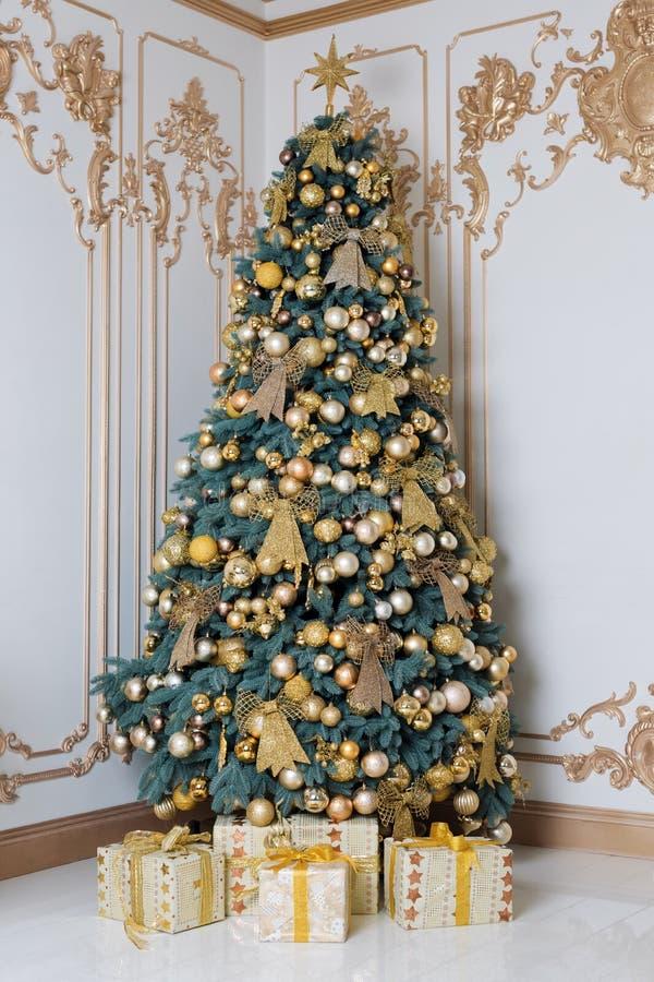 Όμορφο διακοσμημένο χρυσό χριστουγεννιάτικο δέντρο με τα παρόντα κιβώτια στο κλασικό εσωτερικό πολυτέλειας στοκ εικόνα με δικαίωμα ελεύθερης χρήσης
