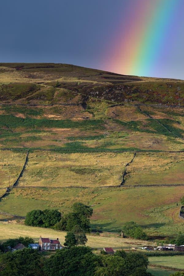 Όμορφο δονούμενο ουράνιο τόξο πέρα από το θυελλώδη δραματικό ουρανό πέρα από το αγγλικό τοπίο επαρχίας στοκ εικόνες