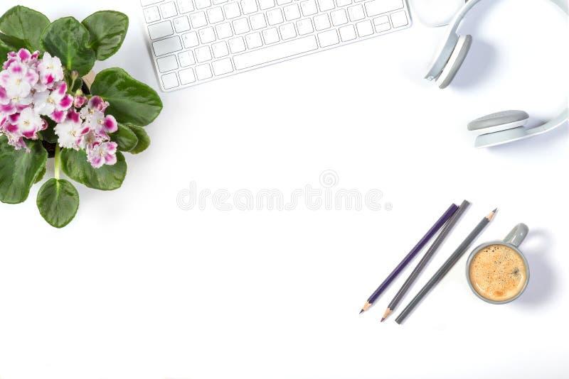Όμορφο ελαφρύ πρότυπο Άσπρο σύγχρονο πληκτρολόγιο, ακουστικά, μολύβια χρώματος, καλό δοχείο λουλουδιών και μικρό γκρίζο φλιτζάνι  στοκ φωτογραφίες
