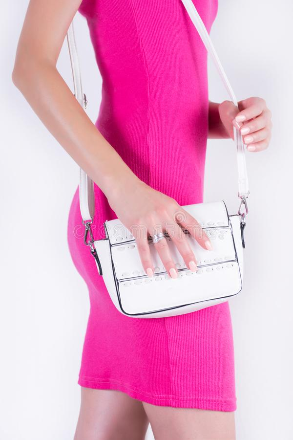 Όμορφο ελκυστικό θηλυκό στο ρόδινο θερινό φόρεμα και την άσπρη τσάντα υπό εξέταση στοκ εικόνες με δικαίωμα ελεύθερης χρήσης