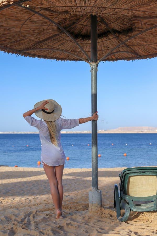 Όμορφο ελκυστικό κορίτσι στο μαγιό και με το ελαφρύ φόρεμα παραλιών που στέκεται μια ηλιόλουστη ημέρα κάτω από μια ομπρέλα αχύρου στοκ φωτογραφία
