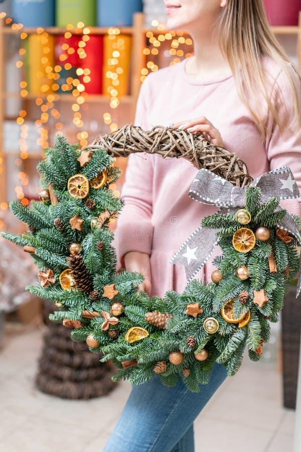 Όμορφο εορταστικό στεφάνι των φρέσκων ερυθρελατών με τα παιχνίδια σφαιρών στα χέρια γυναικών r Bokeh των φω'των γιρλαντών επάνω στοκ φωτογραφίες με δικαίωμα ελεύθερης χρήσης