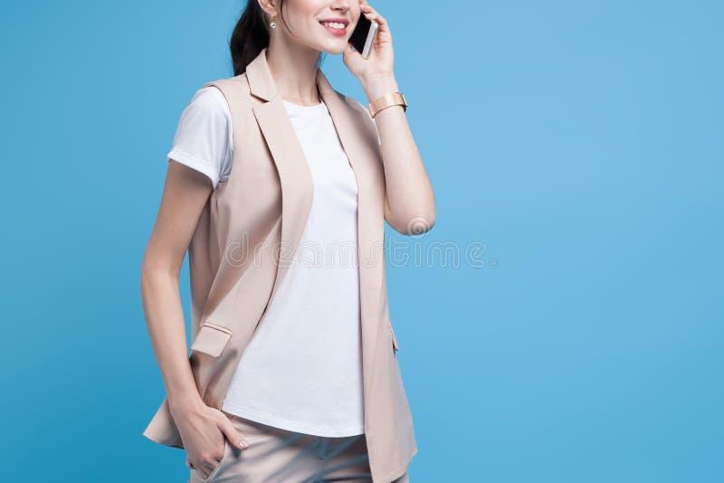 Όμορφο επιτυχές νέο τηλέφωνο χρήσεων επιχειρησιακών γυναικών στην μπλε ΤΣΕ στοκ εικόνα