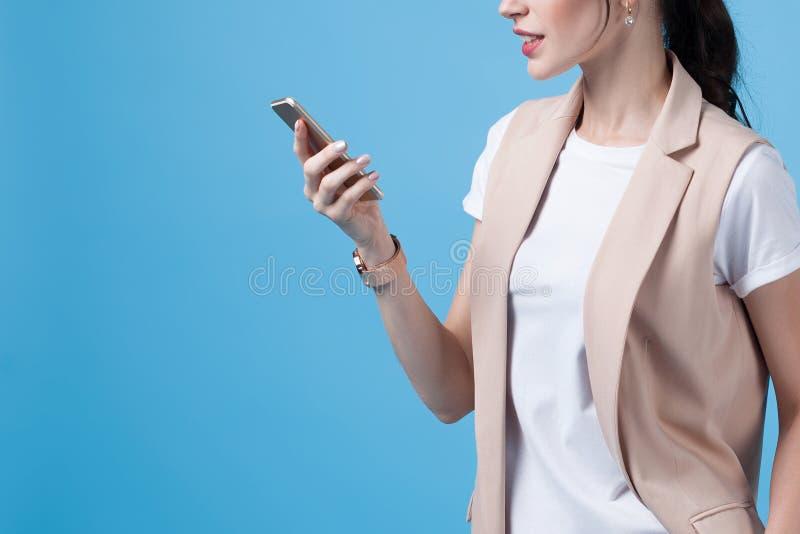 Όμορφο επιτυχές νέο τηλέφωνο χρήσεων επιχειρησιακών γυναικών στην μπλε ΤΣΕ στοκ εικόνες με δικαίωμα ελεύθερης χρήσης