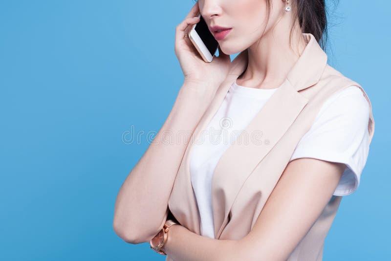 Όμορφο επιτυχές νέο τηλέφωνο χρήσεων επιχειρησιακών γυναικών στην μπλε ΤΣΕ στοκ εικόνες