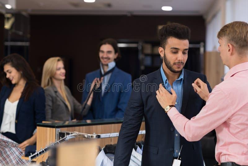 Όμορφο επιχειρησιακό άτομο στις αγορές, νέος αρσενικός βοηθητικός βοηθώντας αγοραστής για να δοκιμάσει το νέο κοστούμι στοκ φωτογραφία