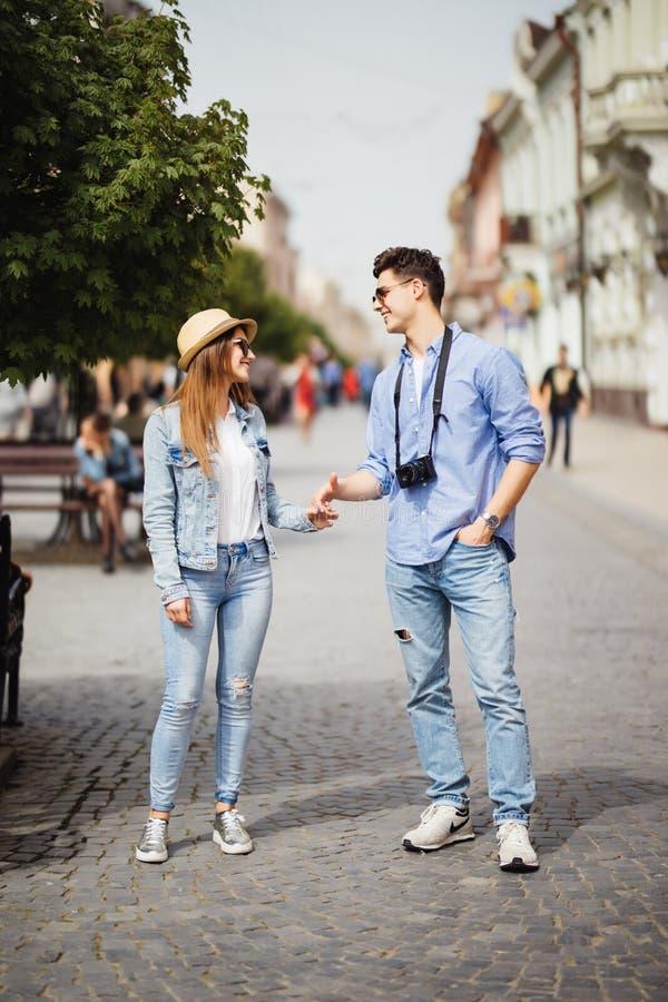 Όμορφο ερωτευμένο περπάτημα ζεύγους τουριστών στην οδό από κοινού Ευτυχής νεαρός άνδρας και χαμογελώντας γυναίκα που περπατούν γύ στοκ φωτογραφία