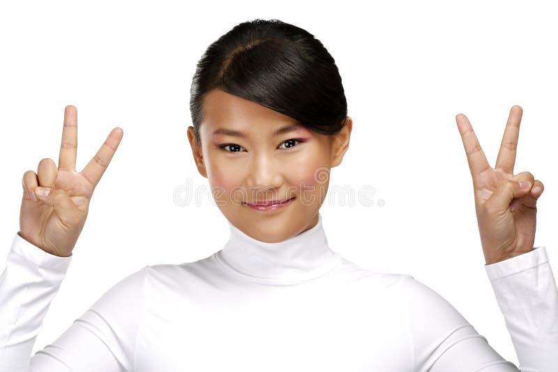 Όμορφο ευτυχές ασιατικό κορίτσι που παρουσιάζει θετικό σημάδι νίκης στοκ φωτογραφία