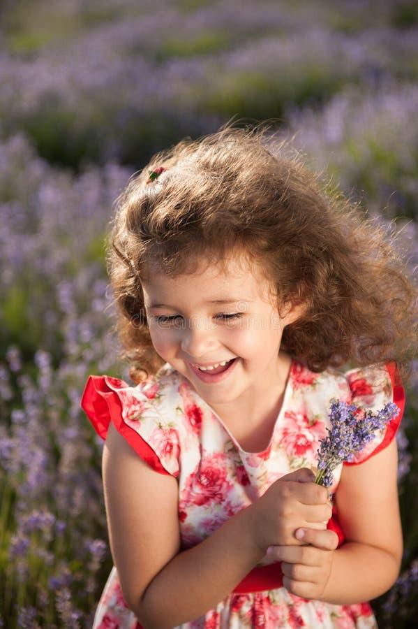 Όμορφο ευτυχές γελώντας μικρό κορίτσι με την ανθοδέσμη των λουλουδιών lavender στον τομέα στοκ εικόνα
