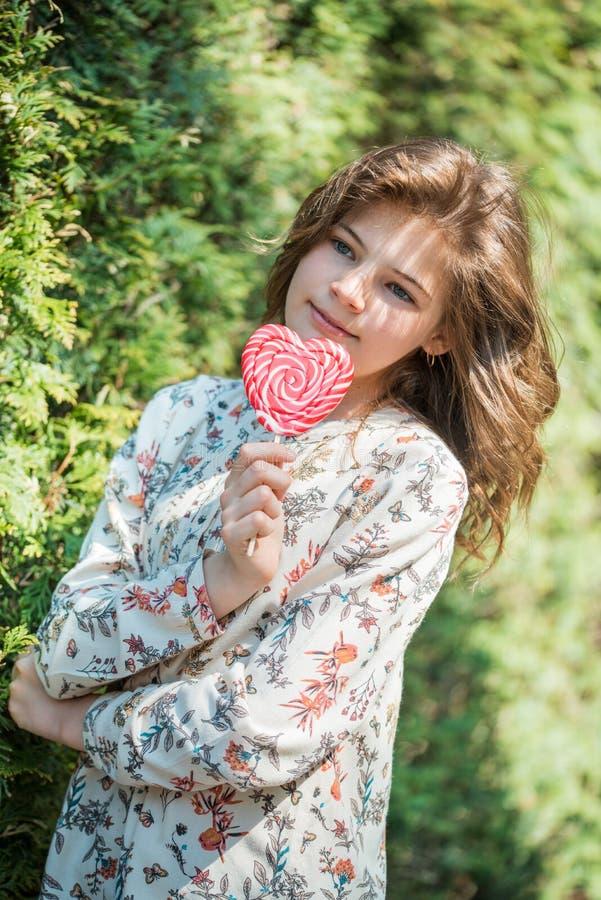 Όμορφο ευτυχές κορίτσι με μια μεγάλη κόκκινη καραμέλα σε ένα ραβδί, ένα χαμόγελο και ένα γέλιο συρμένο απομονωμένο χέρι διανυσματ στοκ φωτογραφία με δικαίωμα ελεύθερης χρήσης