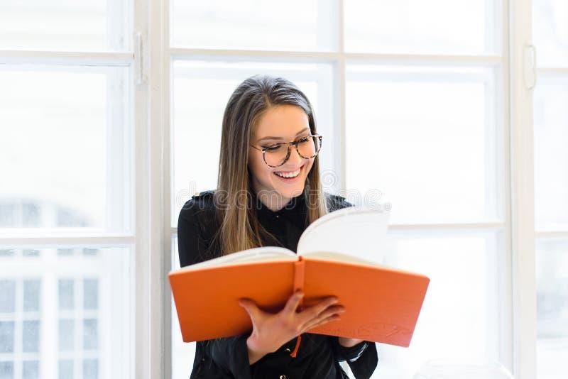 Όμορφο ευτυχές κορίτσι σπουδαστών στα γυαλιά που διαβάζει το βιβλίο στο windowsill στοκ εικόνα